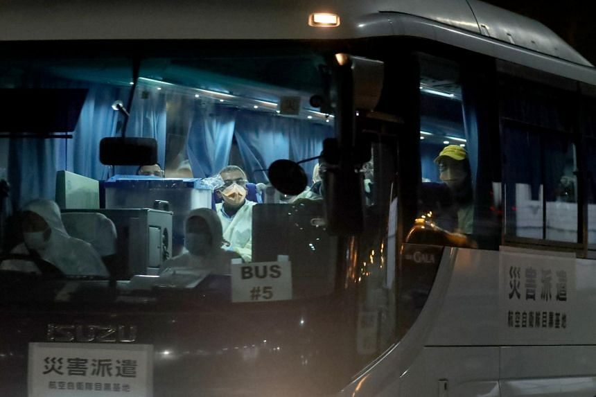 People wearing face masks sit in a bus believed to be carrying Australian passengers from the cruise ship Diamond Princess, as it leaves Daikoku Pier Cruise Terminal in Yokohama, south of Tokyo, on Feb 19, 2020.