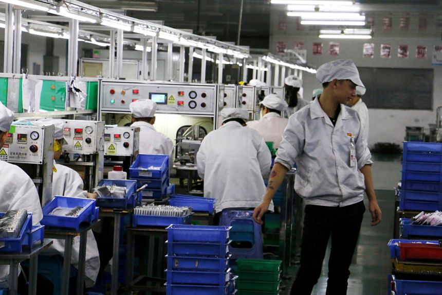 In a photo from Oct 16, 2018, employees work at a production line of lithium ion batteries inside a factory in Dongguan, Guangdong province, China.