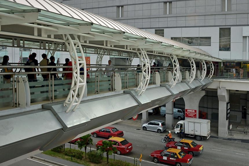 People at the link bridge between JB Sentral and City Square Mall near Woodlands checkpoint.