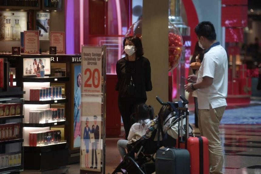 Visitors wearing masks as they shop at the duty-free stores in the transit area at Changi Airport Terminal 3 on Feb 14, 2020.