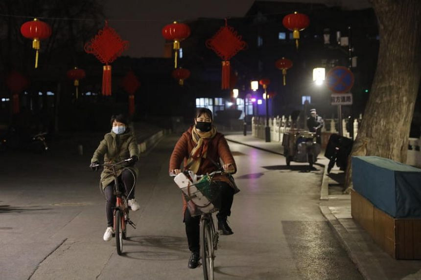 In a photo taken on Feb 20, 2020, people with protective masks ride bicycles at Houhai Bar Street in Beijing.