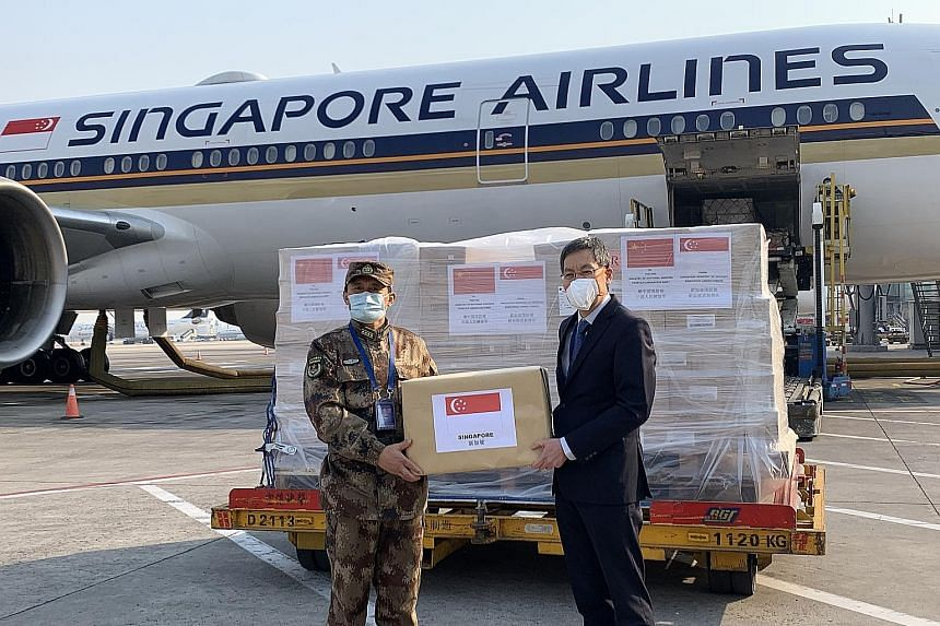 Singapore Ambassador to China Lui Tuck Yew (right) handing over the Republic's humanitarian assistance to People's Liberation Army General Hospital Medical Service Department deputy head Zhang Fu in Beijing on Wednesday.