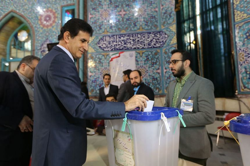 An Iranian man casts his vote in a parliamentary election at a polling station in Teheran on Feb 21, 2020.