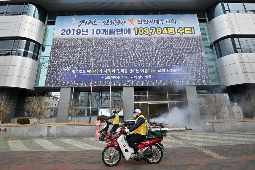 South Korean health officials spray disinfectant in front of the Daegu branch of the Shincheonji Church of Jesus, on Feb 21, 2020.