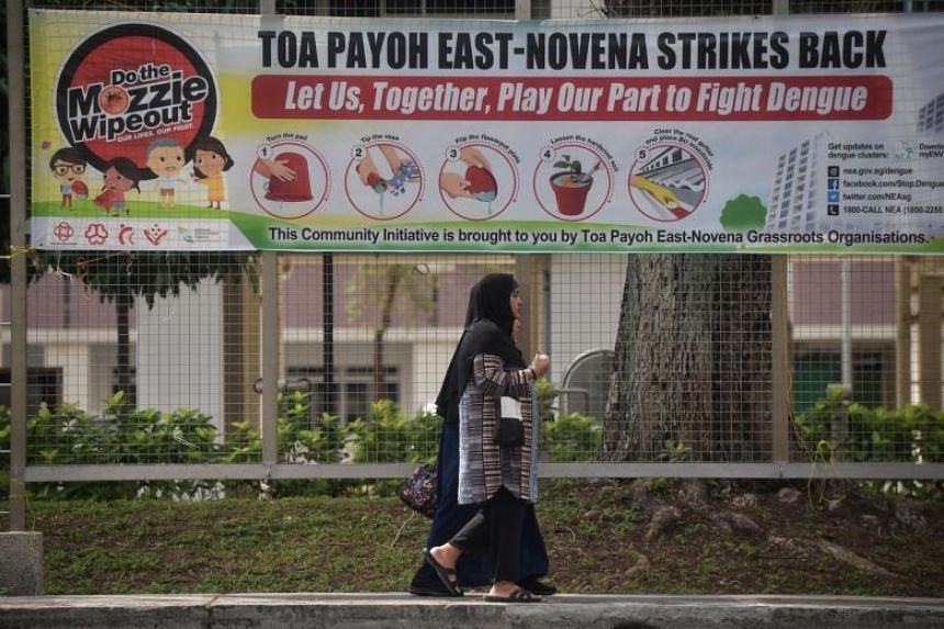 """A photo from Jan 14, 2020, shows women walking past a """"Do the Mozzie Wipeout"""" banner promoting ways to prevent mosquito breeding at Kim Keat Avenue."""
