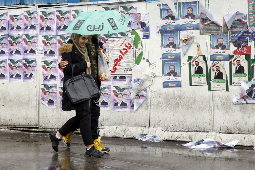 People walk past electoral posters in Teheran on Feb 20, 2020, the day before Iranian parliamentary elections.