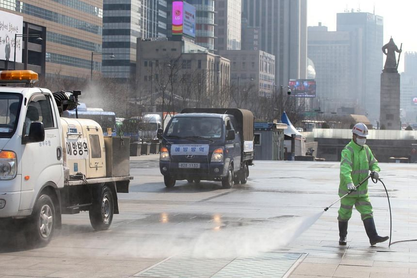 Officials disinfect a street at Gwanghwamun square in Seoul, South Korea, on Feb 20, 2020.