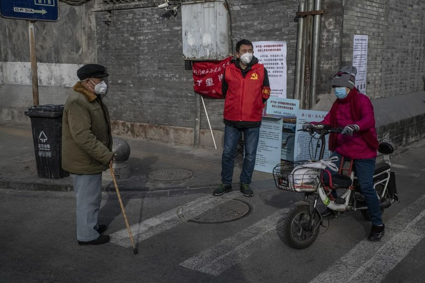 A volunteer in Beijing guards the entrance to a residential street, on Feb 18, 2020.