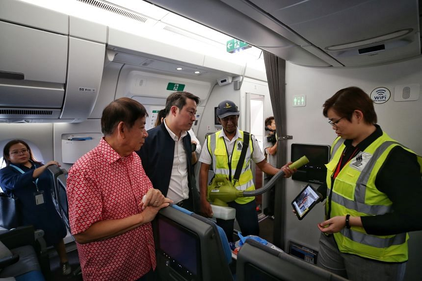 Transport Minister Khaw Boon Wan (left) and Senior Minister of State for Health and Transport Lam Pin Min observing a fogging process on a tablet on a Singapore Airlines plane.