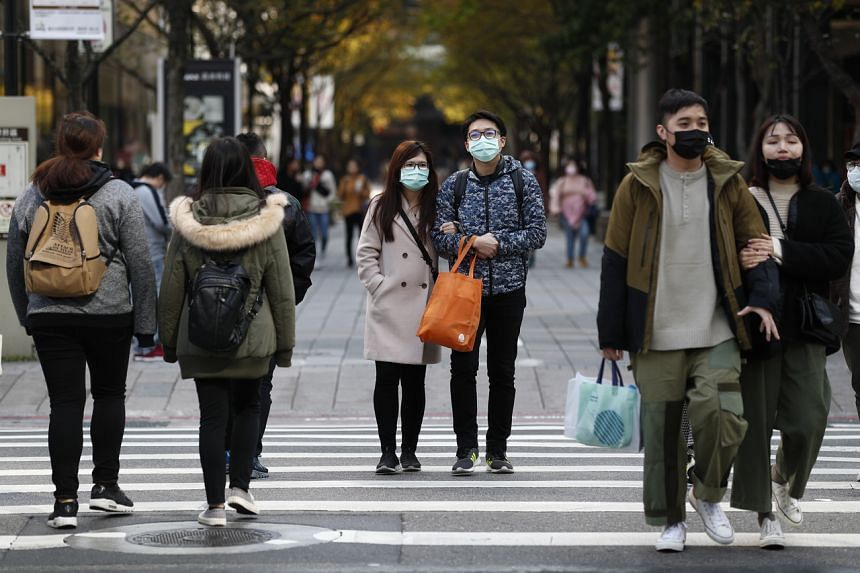 People wearing masks cross the street in Taipei, Taiwan, on Feb 17, 2020.