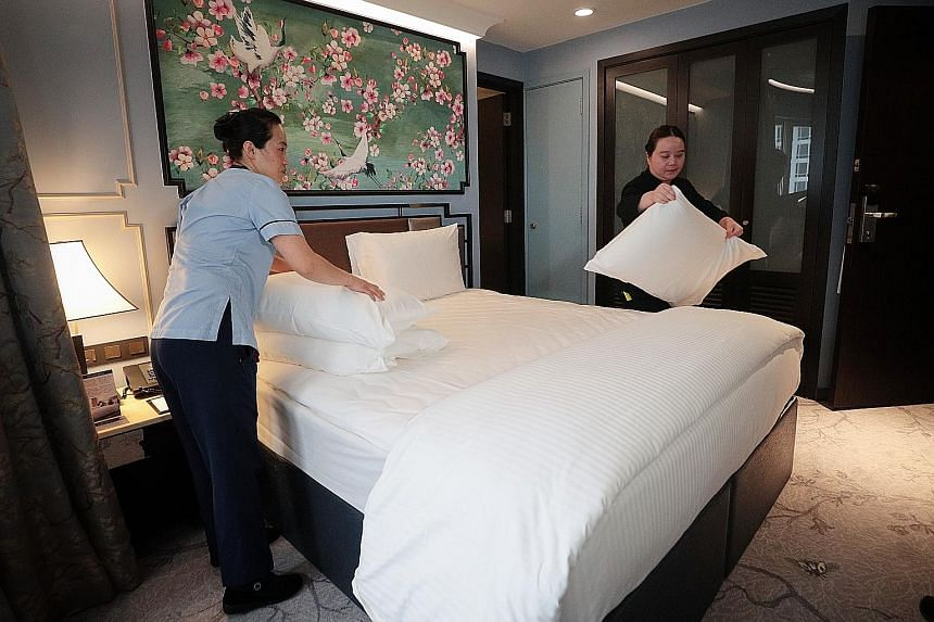 The measures to ease the impact of the coronavirus outbreak, including salary support for hotels that send staff for training, are expected to benefit those in the tourism sector like Copthorne King's Hotel's room attendant Vicky Zhang (left) and ass