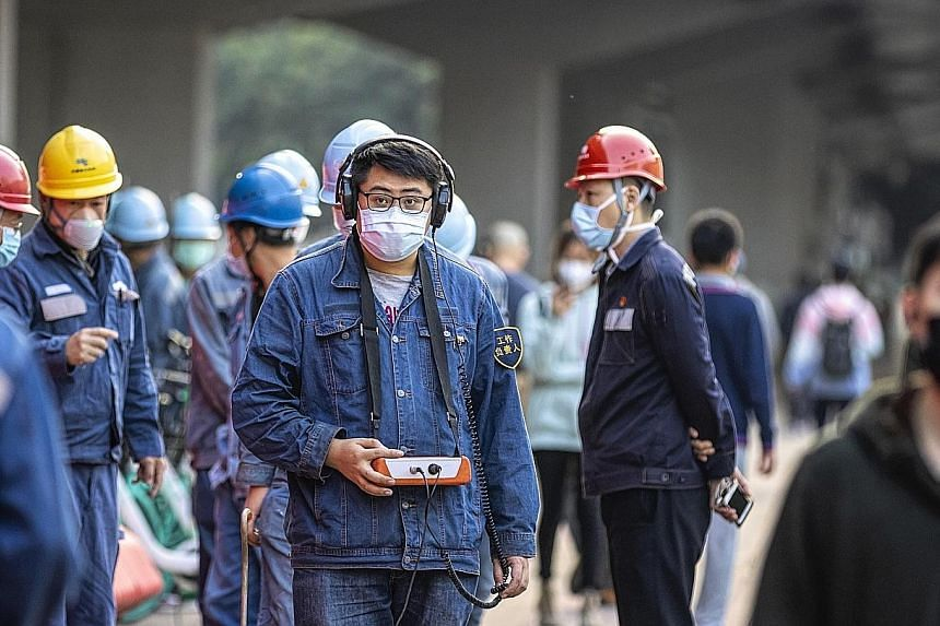 Workers wearing masks in Guangzhou. The coronavirus outbreak has resulted in the temporary closure of some businesses in China.