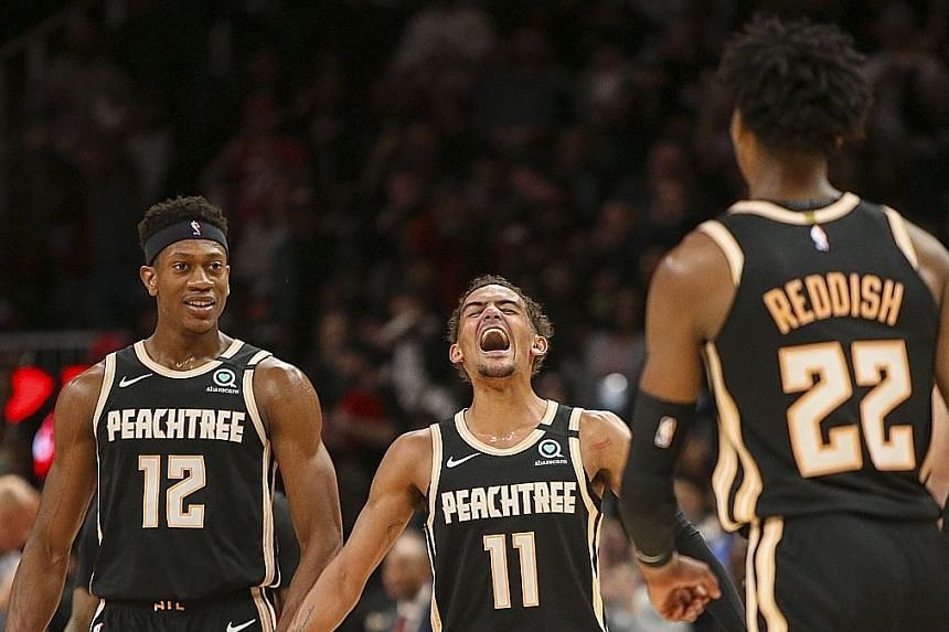 Atlanta Hawks guard Trae Young (centre) celebrating with De'Andre Hunter after a basket by guard Cam Reddish against Miami Heat at the State Farm Arena. The 21-year-old became the fourth-youngest player to score 50 points after LeBron James, Devin Bo