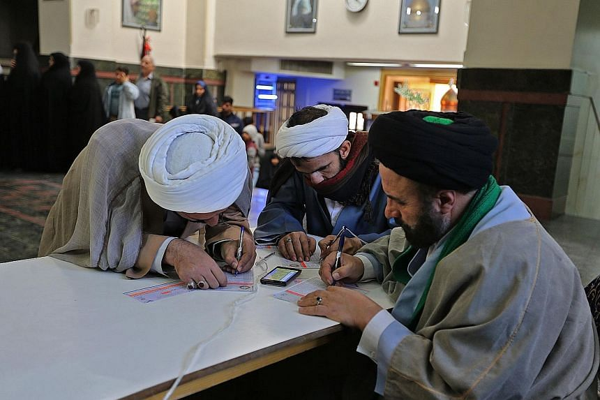 """Iranians casting their votes at the Shah Abdul Azim shrine in Teheran yesterday. President Hassan Rouhani has urged his people to demonstrate """"victory"""" by voting in large numbers."""
