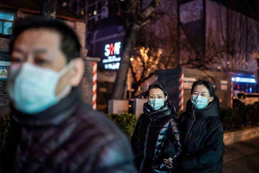 People wearing protective face masks walk on a street in Beijing on Feb 21, 2020.