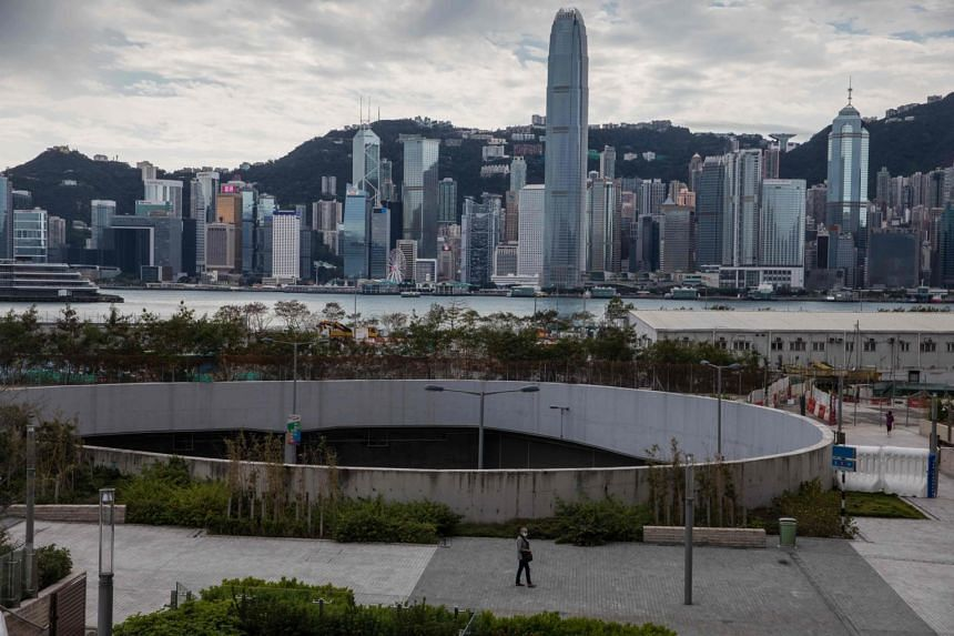 In a photo taken on Jan 26, 2020, a woman wearing a face mask walks before the city skyline in Hong Kong.
