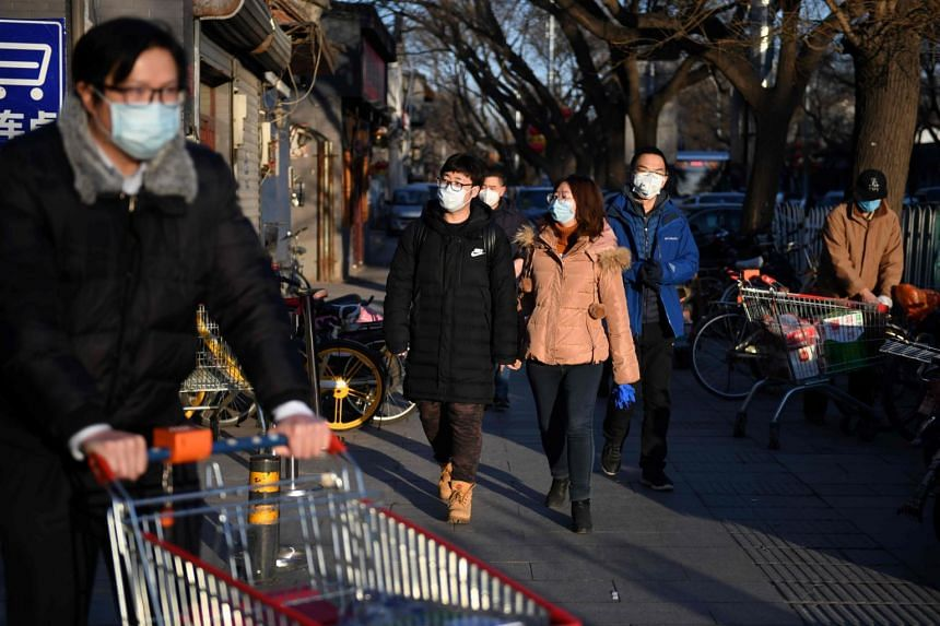 People wear protective face masks as they arrive at a market in Beijing on Feb 17, 2020.
