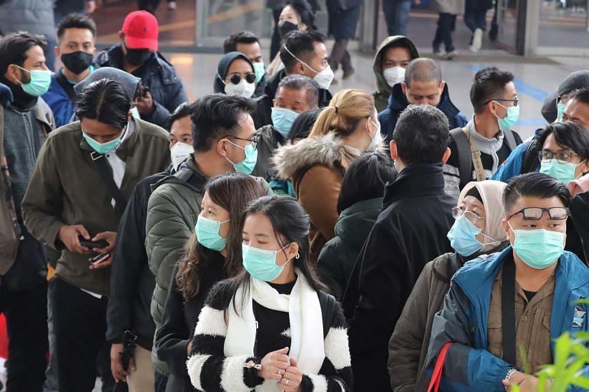 Os turistas que usam máscaras aguardam um trem na estação de Seul, em Seul, Coréia do Sul, em 21 de fevereiro de 2020.