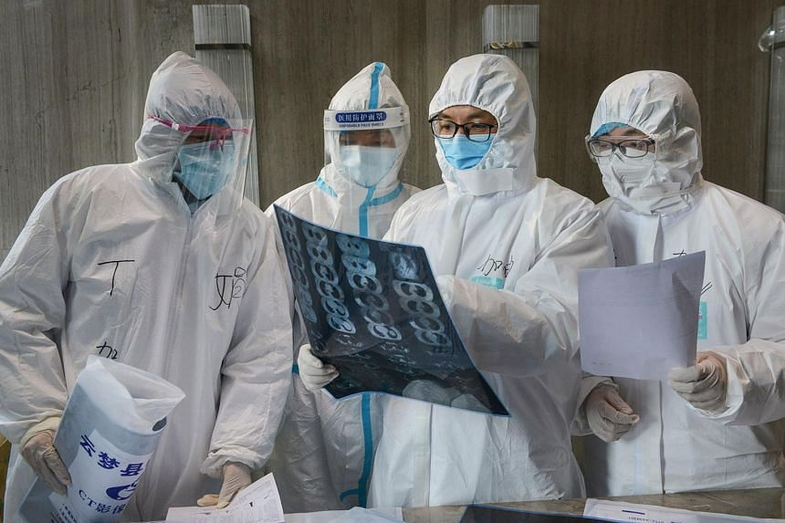 A photo taken on Feb 20, 2020, shows doctors looking at a lung CT image at a hospital in Xiaogan, Hubei.