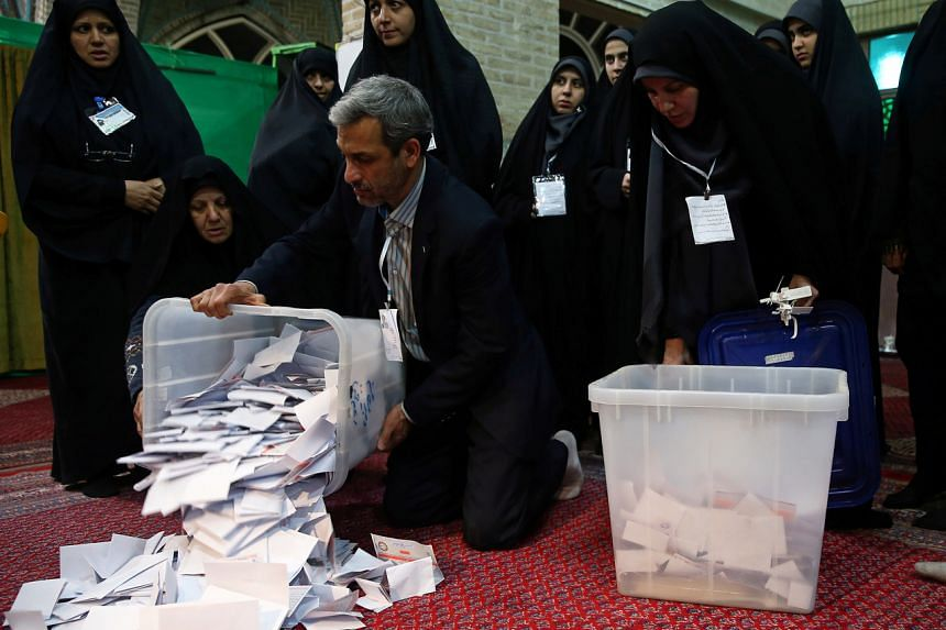 Poll workers empty full ballot boxes after the parliamentary election voting ended in Teheran, on Feb 22, 2020.