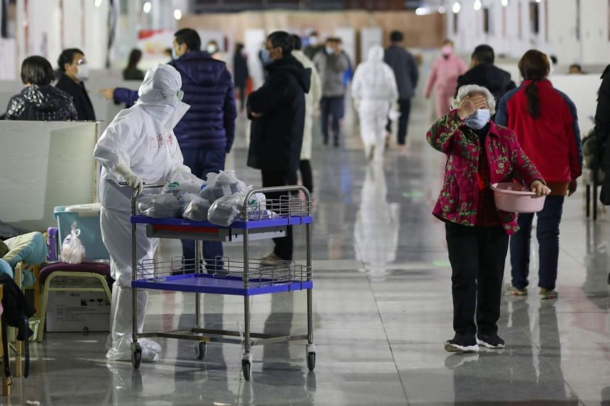 A nurse distributes medicine to patients at a temporary hospital situated in the Tazihu Gymnasium in Wuhan, Hubei province, China, on Feb 21, 2020.