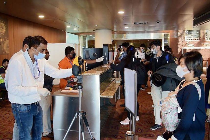 Airport officials checking passengers' temperatures amid the ongoing coronavirus situation, at the Chhatrapati Shivaji Maharaj International Airport (CSMIA) in Mumbai on Feb 19, 2020.