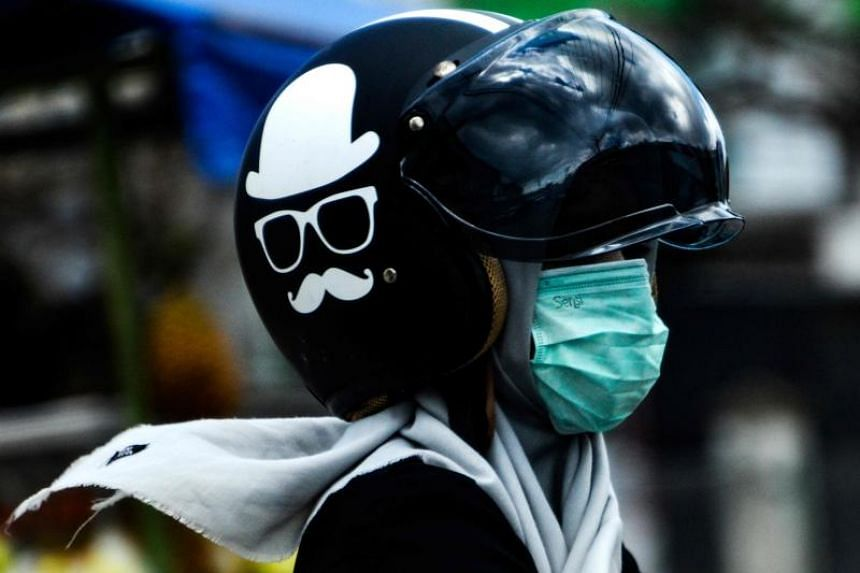 A woman wearing a protective face mask and a helmet at a market in Banda Aceh, Indonesia, on Feb 21, 2020.