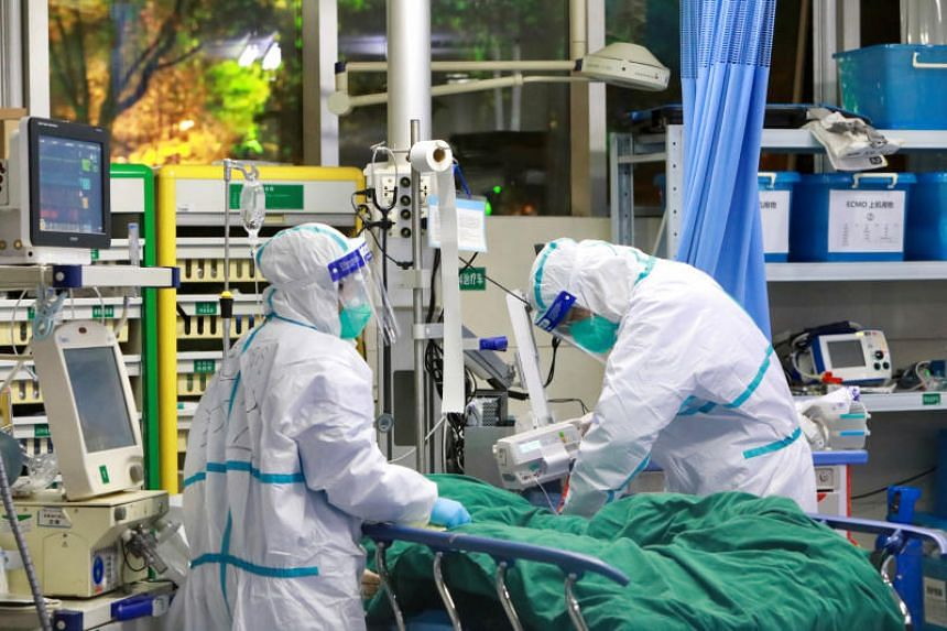 Medical staff in protective suits treat a patient with pneumonia caused by the new coronavirus at the Zhongnan Hospital of Wuhan University, in Wuhan on Jan 28, 2020.