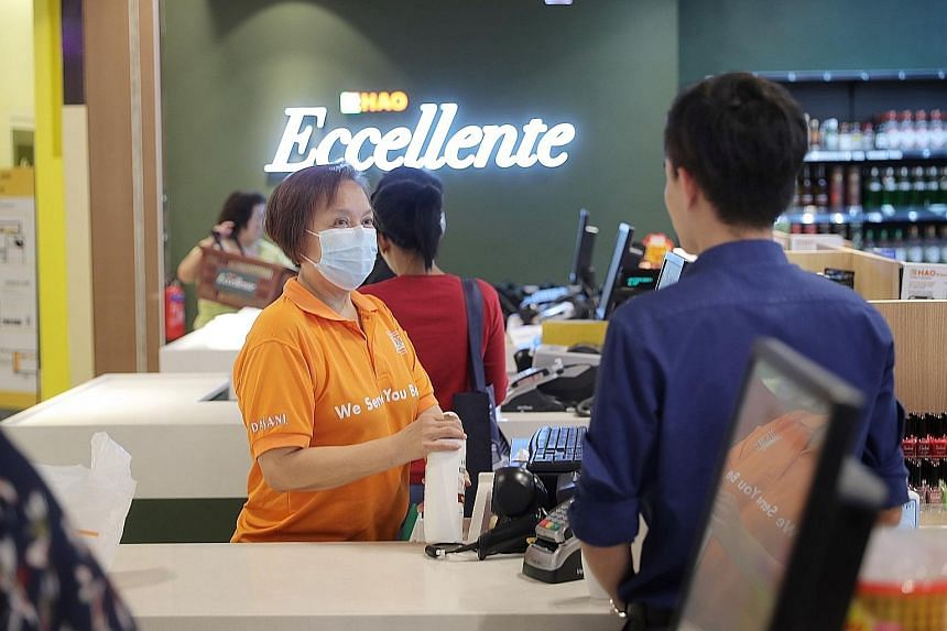 Cashier Joanne Sim at the Eccellente outlet in Kinex Shopping Mall. The 58-year-old, who takes vitamin C tablets daily to boost her immunity and dons a mask during work, said she is not worried about falling sick. ST PHOTO: GAVIN FOO