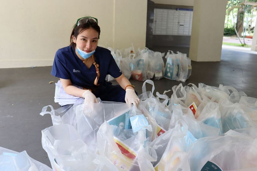 Singaporean socialite Kim Lim distributing care packages containing hand sanitisers, Dettol soap bottles and biscuits to elderly citizens.