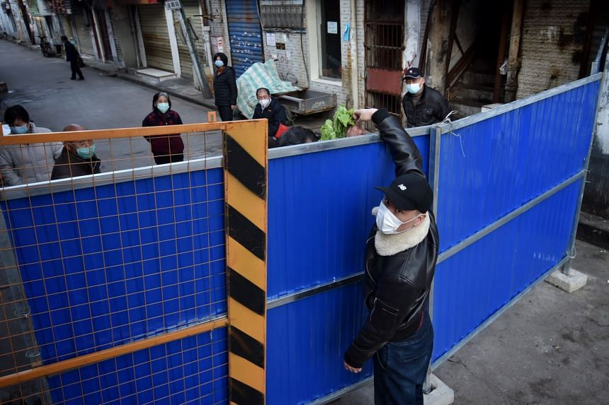 A masked man passes groceries over a temporary wall around a residential block in Wuhan, China, on Feb 23, 2020.