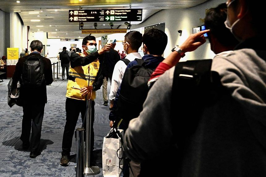 An Indonesian health official takes temperature readings of arriving passengers amid concerns of the coronavirus outbreak at the Jakarta international Airport on Feb 23, 2020.