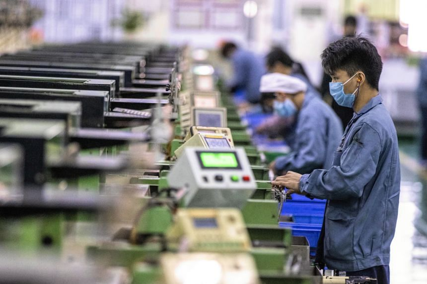 People wearing face masks work in the Galanz factory in Foshan, China, on Feb 18, 2020.