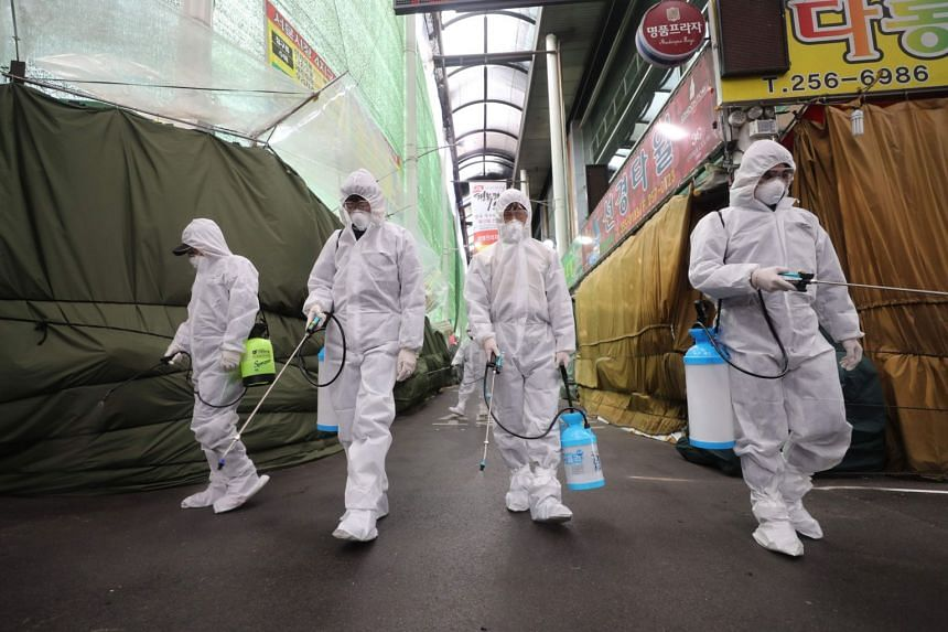 Workers wearing protective gear spray disinfectant at a market in Daegu, South Korea, on Feb 23, 2020
