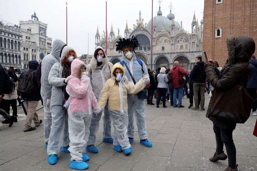 Carnival revellers wear protective face masks at Venice Carnival, on Feb 23, 2020.