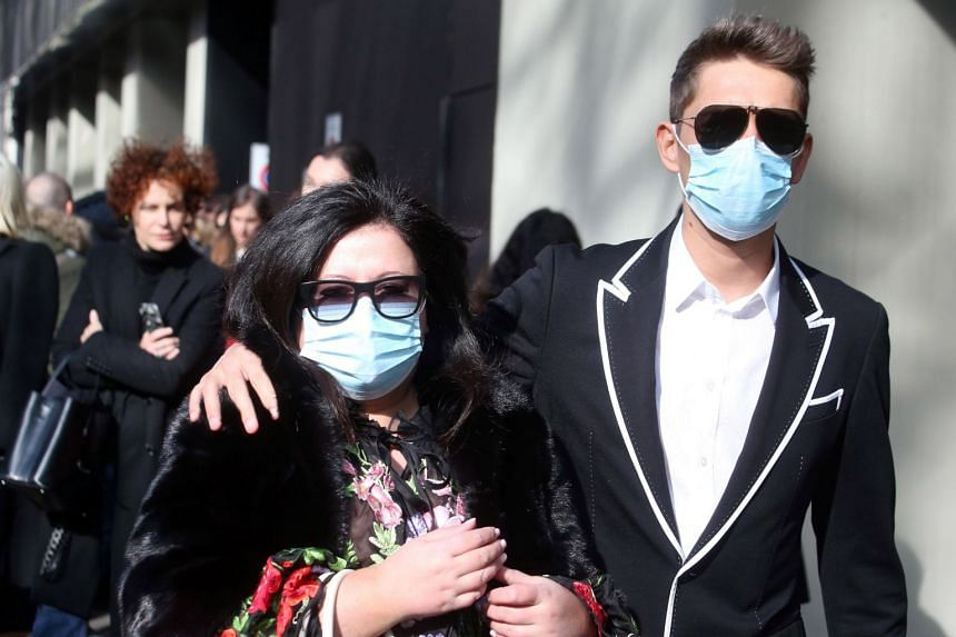 Guests wear face masks to protect against coronavirus upon arrival to attend the Dolce and Gabbana show during the Milan Fashion Week, on Feb 23, 2020.