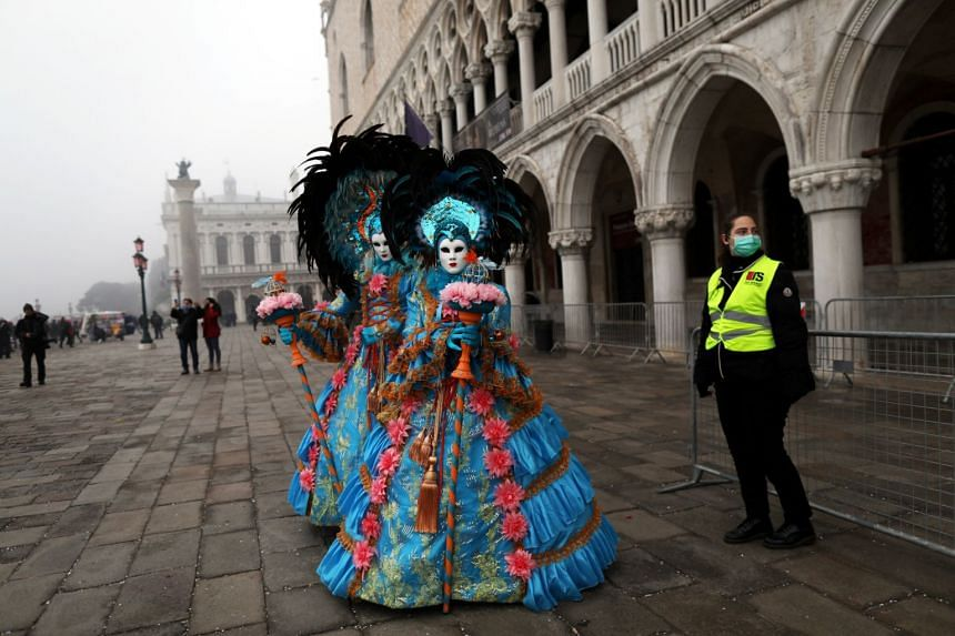 A policewoman wearing a protective mask stands next to carnival revellers at Venice Carnival, on Feb 23, 2020.