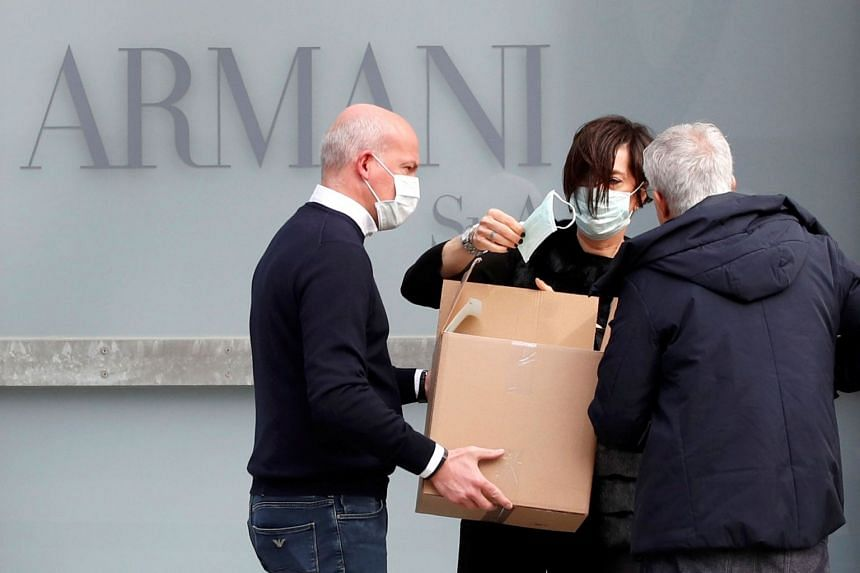 A worker holds a face mask outside the theatre where the Italian designer Giorgio Armani said his Milan Fashion Week show would take place to safeguard the health of press and buyers, on Feb 23, 2020.