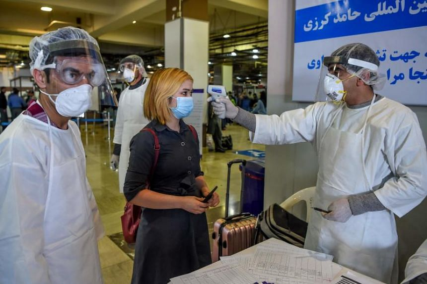 Staff in protective gear screen a passenger at Hamid Karzai International Airport in Kabul on Feb 2, 2020.