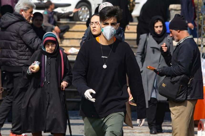 A young Iranian man wearing a protective mask, walks in a busy street in Teheran, Iran, on Feb 22, 2020.