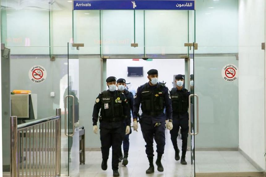 A photo taken on Feb 22, 2020, shows Kuwaiti policemen with masks at Sheikh Saad Airport in Kuwait City. Kuwait and Bahrain confirmed the first cases of novel coronavirus, with the infection detected in people returning from Iran.