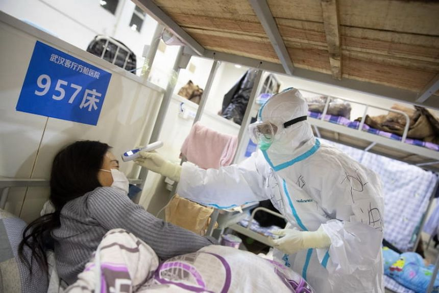 A photo taken on Feb 17, 2020, shows a medical worker attending to a patient at the Wuhan Fang Cang makeshift hospital in China.
