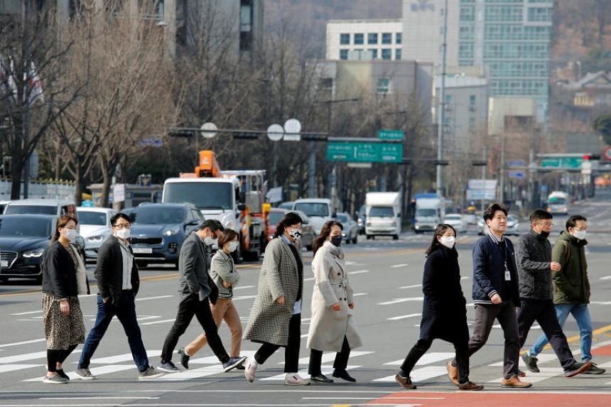 Pedestrians in downtown Seoul on Feb 24, 2020. South Korea is the hardest-hit nation outside China by the coronavirus outbreak, with 833 cases and seven deaths.