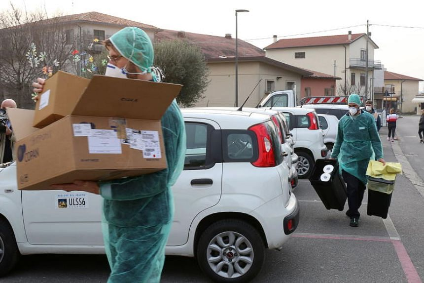 Medical workers near a closed elementary school in Vo' Euganeo, Italy, on Feb 23, 2020.