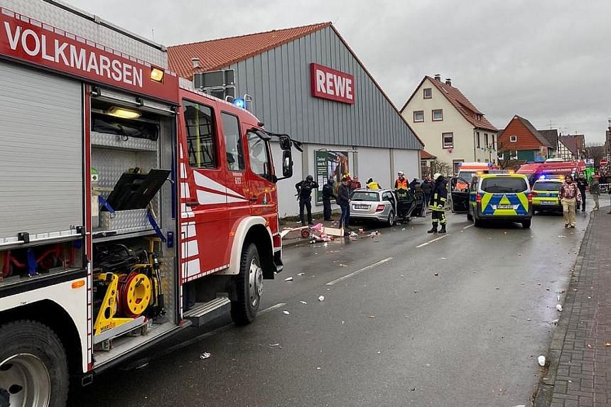 Police officers and rescue vehicles next to a silver vehicle with its doors open, after the Volkmarsen incident in which some people were hurt.