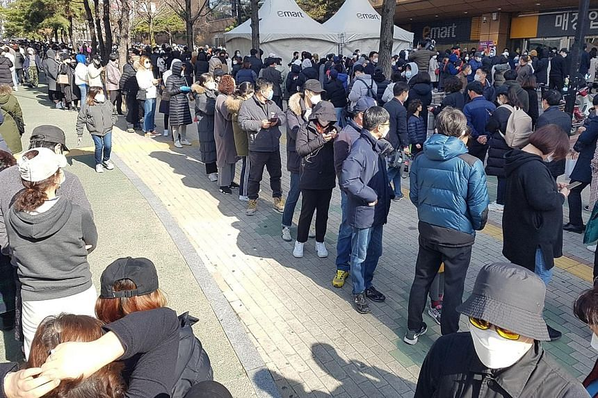 People waiting to buy masks at a market in Daegu, South Korea, yesterday. South Korea has raised its virus alert to the highest red as the number of cases continues to spike, hitting 833 yesterday, with more than half linked to a cluster of infection