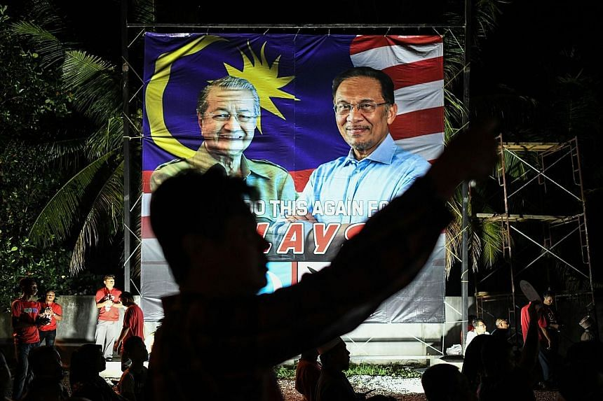A banner during Malaysia's 2018 General Election showing Tun Dr Mahathir Mohamad (far left) and Datuk Seri Anwar Ibrahim running as part of Pakatan Harapan. Tensions have since plagued the coalition, causing it to break up.