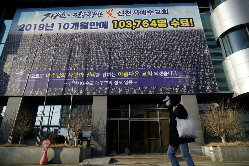 A man wearing a mask to prevent contracting the coronavirus walks past a branch of the Shincheonji Church of Jesus in Daegu, South Korea, on Feb 21, 2020.