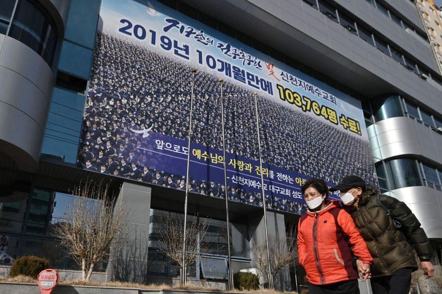 People walk past the Shincheonji Church of Jesus in Daegu, South Korea, on Feb 24, 2020.