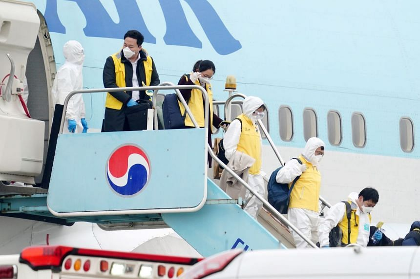 South Korean officials wearing protective gear disembark a chartered plane after its arrival in Seoul from Wuhan, China, on Feb 1, 2020.